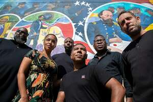 """Reginald Adams, center, with his creative team, in front of his a 5,000-square-foot mural, entitled """"Absolute Equality,"""" in Galveston, Texas, on May 5, 2021. On June 19, 1865, a Union general issued an order that led to the freeing of slaves in Texas and a new mural will now mark the spot where it happened.(Montinique Monroe/The New York Times)"""
