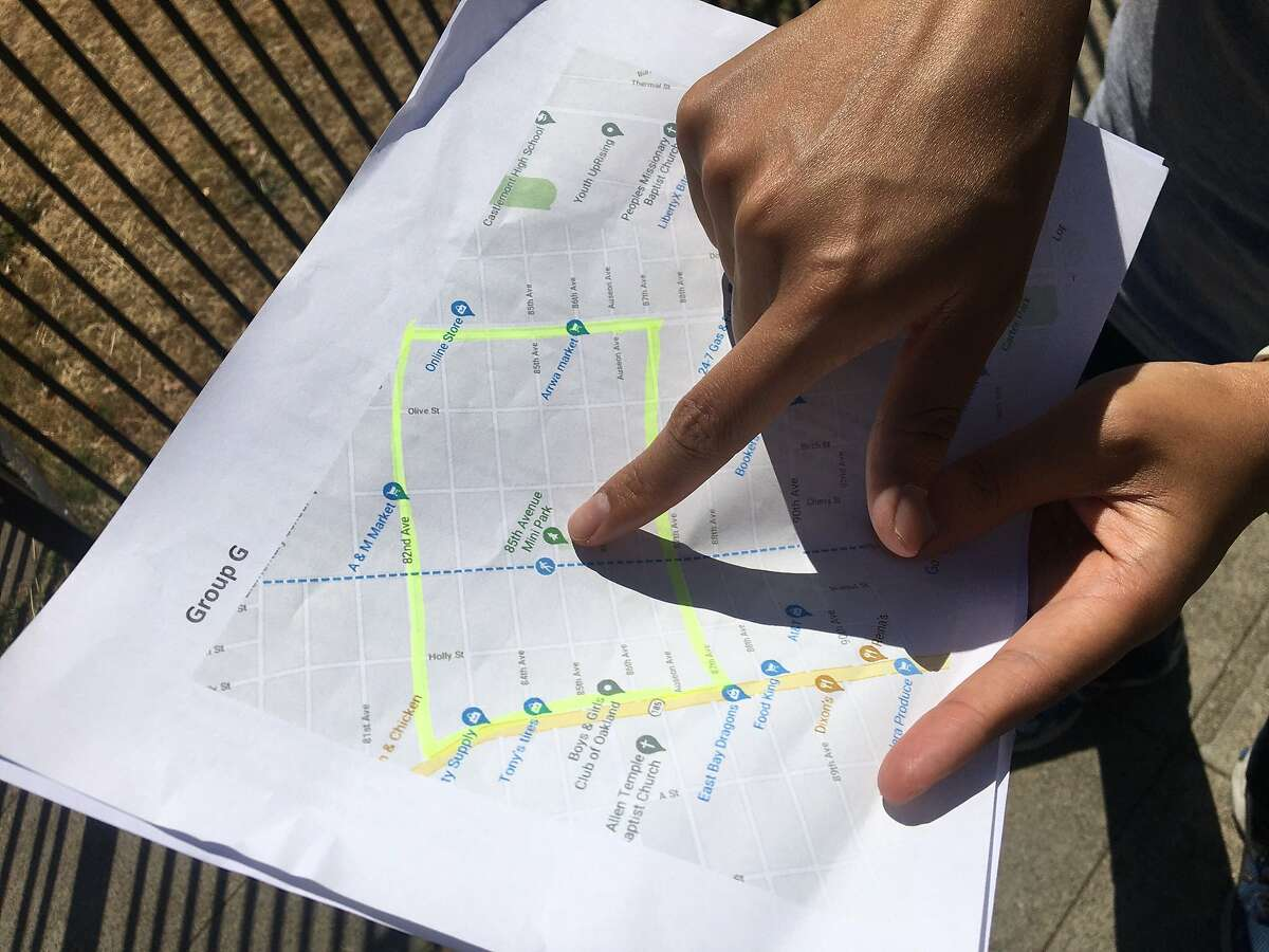 Oakland City Council Member Loren Taylor consults a map of the East Oakland neighborhood being canvassed to get the word out about a city-run guaranteed income pilot program now accepting applicants.