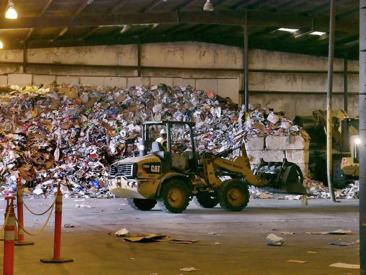 An employee of the Laredo Solid Waste Department uses a backhoe to pile the recyclable material that is deposited at the recycling center.