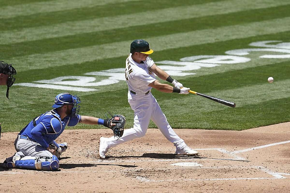 Oakland Athletics' Matt Chapman, right, hits a two-run double in front of Kansas City Royals catcher Cam Gallagher during the second inning of a baseball game in Oakland, Calif., Saturday, June 12, 2021. (AP Photo/Jeff Chiu)