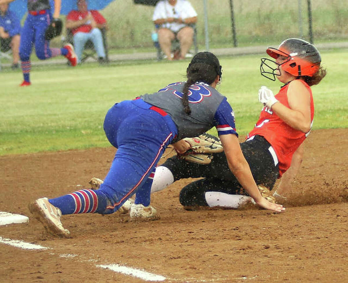 Gillespie's Regan Bussmann (right) is tagged out attempting to steal third by Nashville third baseman Whitley Hunter during a steady rain with nobody out in the first inning of a Class 2A sectional semifinal last Tuesday in Gillespie.