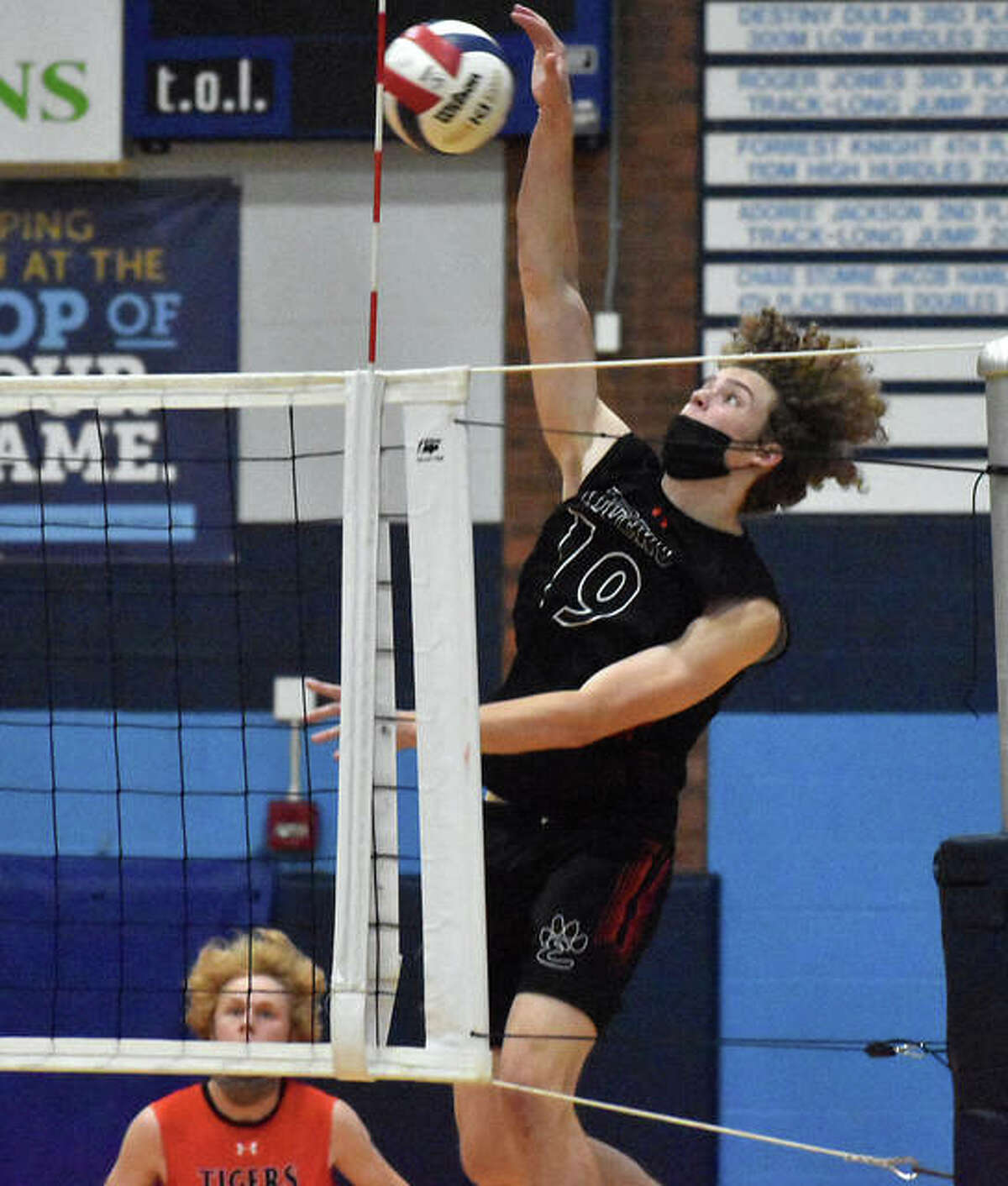 Edwardsville's Evan Reid slams down the first of his five kills in the third set against O'Fallon.