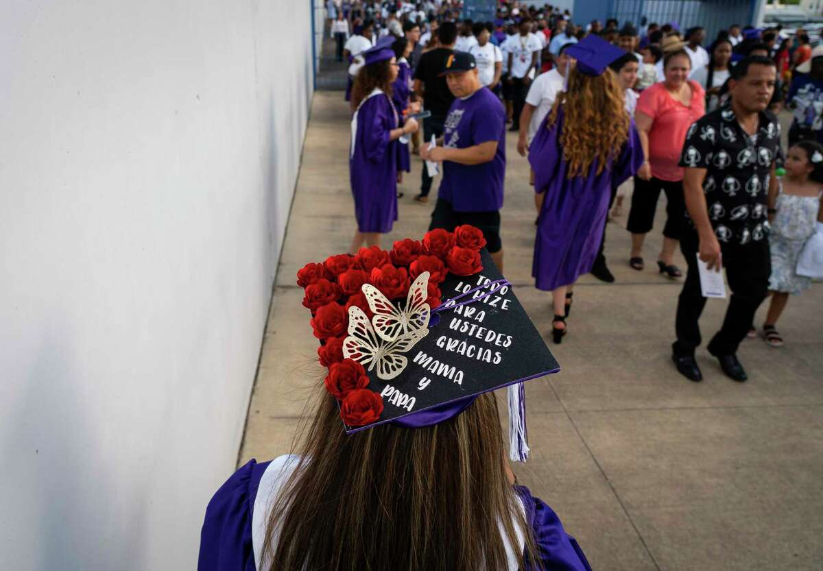 Lizbeth Contreras Tovar, right, walks around the stadium towards the exit to find her family after her commencement ceremony for Wheatley High School on Saturday, June 12, 2021, at Barnett Stadium in Houston.