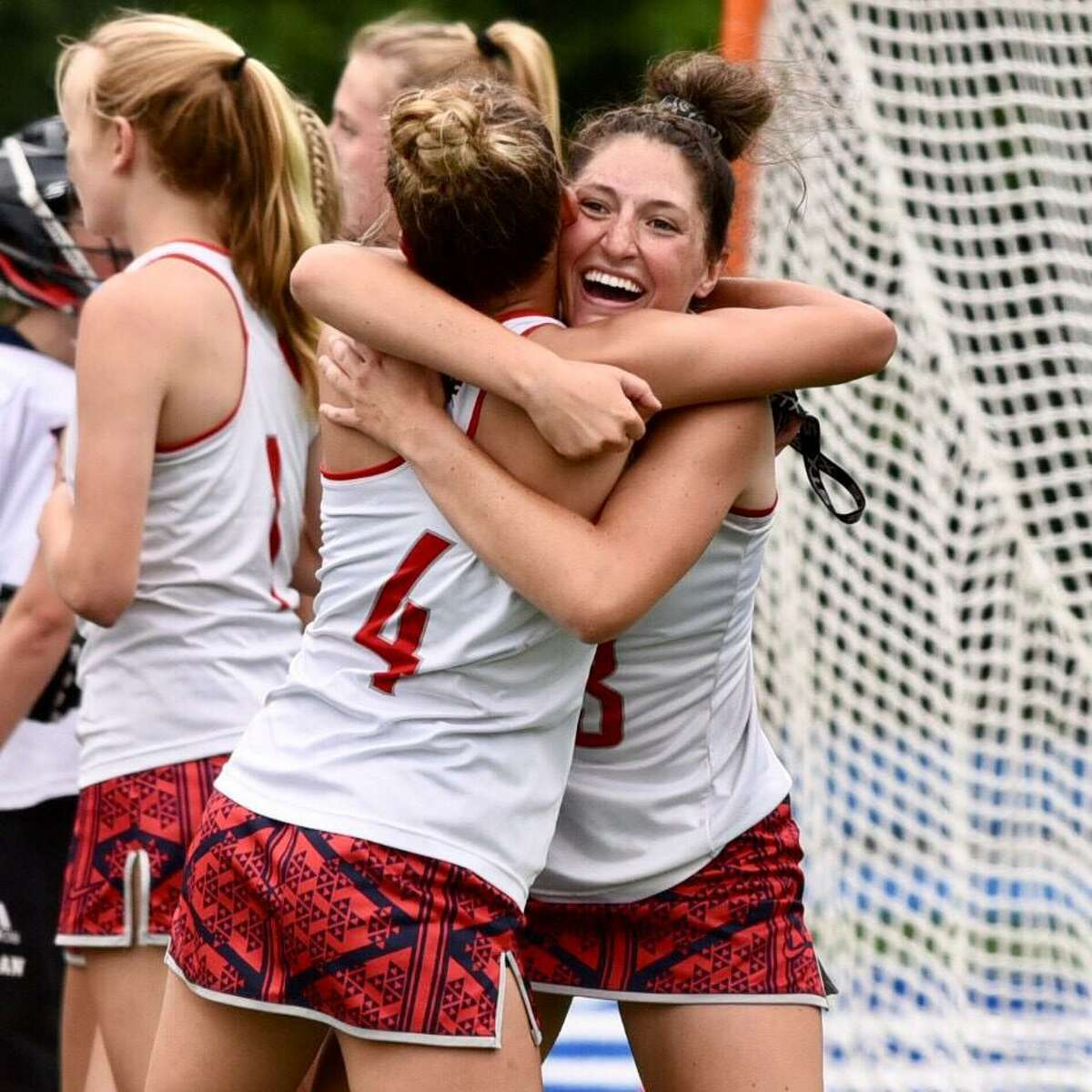 New Fairfield's Jordan Siemonsen (4) and Reagan Tenaglia celebrate their 11-8 win over Weston for the Class S girls lacrosse championship on Saturday at Bunnell in Stratford.