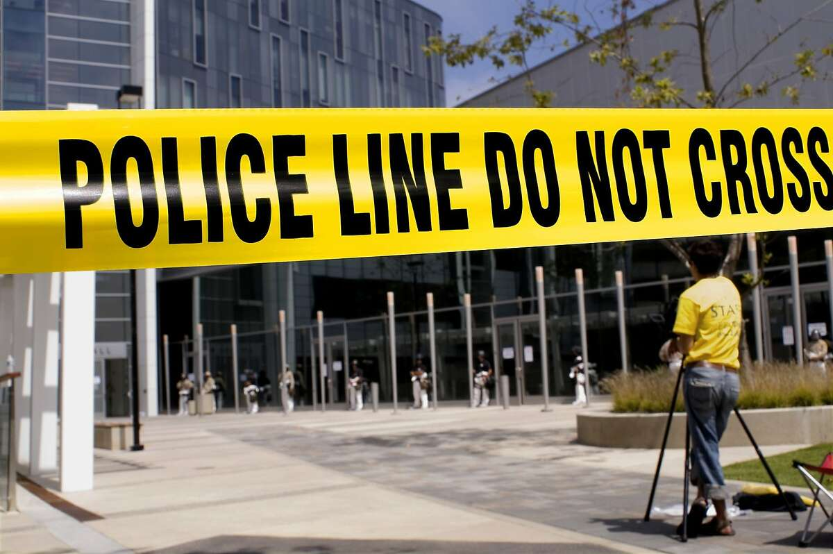 Crime scene tape with a camerman in the near background and a SWAT team in the far background.