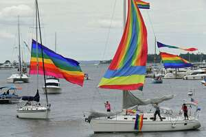 Participants in the Pride Parade of Sail motor through Norwalk Harbor Saturday.
