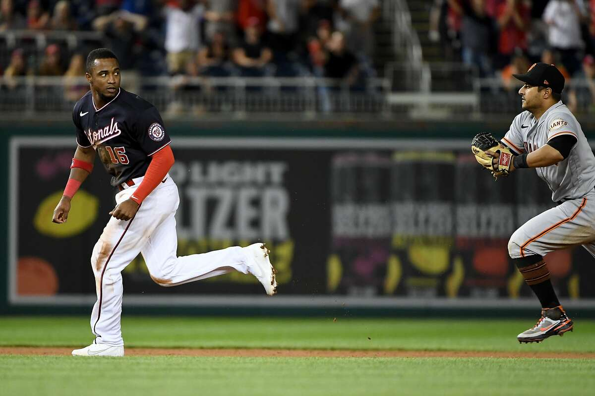 WASHINGTON, DC - JUNE 12: Victor Robles #16 of the Washington Nationals is caught in a run down by Donovan Solano #7 of the San Francisco Giants after over sliding second base during the eighth inning of a doubleheader at Nationals Park on June 12, 2021 in Washington, DC. (Photo by Will Newton/Getty Images)