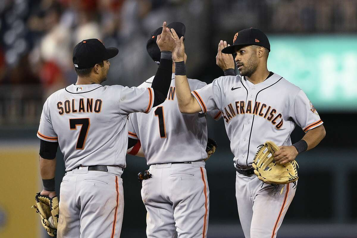 San Francisco Giants' LaMonte Wade Jr, right, and Donovan Solano (7) celebrate after the second baseball game of the team's doubleheader against the Washington Nationals, Saturday, June 12, 2021, in Washington. The Giants won 2-1 in eight innings. (AP Photo/Nick Wass)