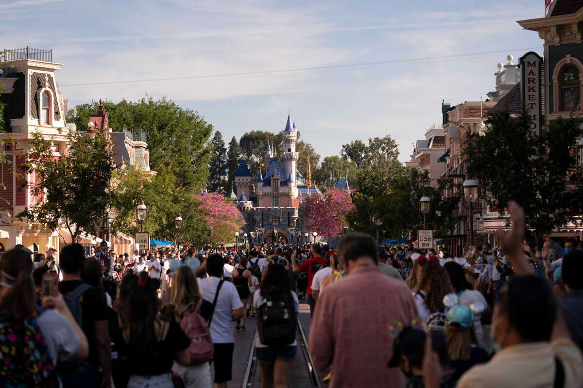 Guests walk along Main Street USA on the first day back at Disneyland in Anaheim. The theme park was closed under the state's strict virus rules until it was allowed to open April 30.