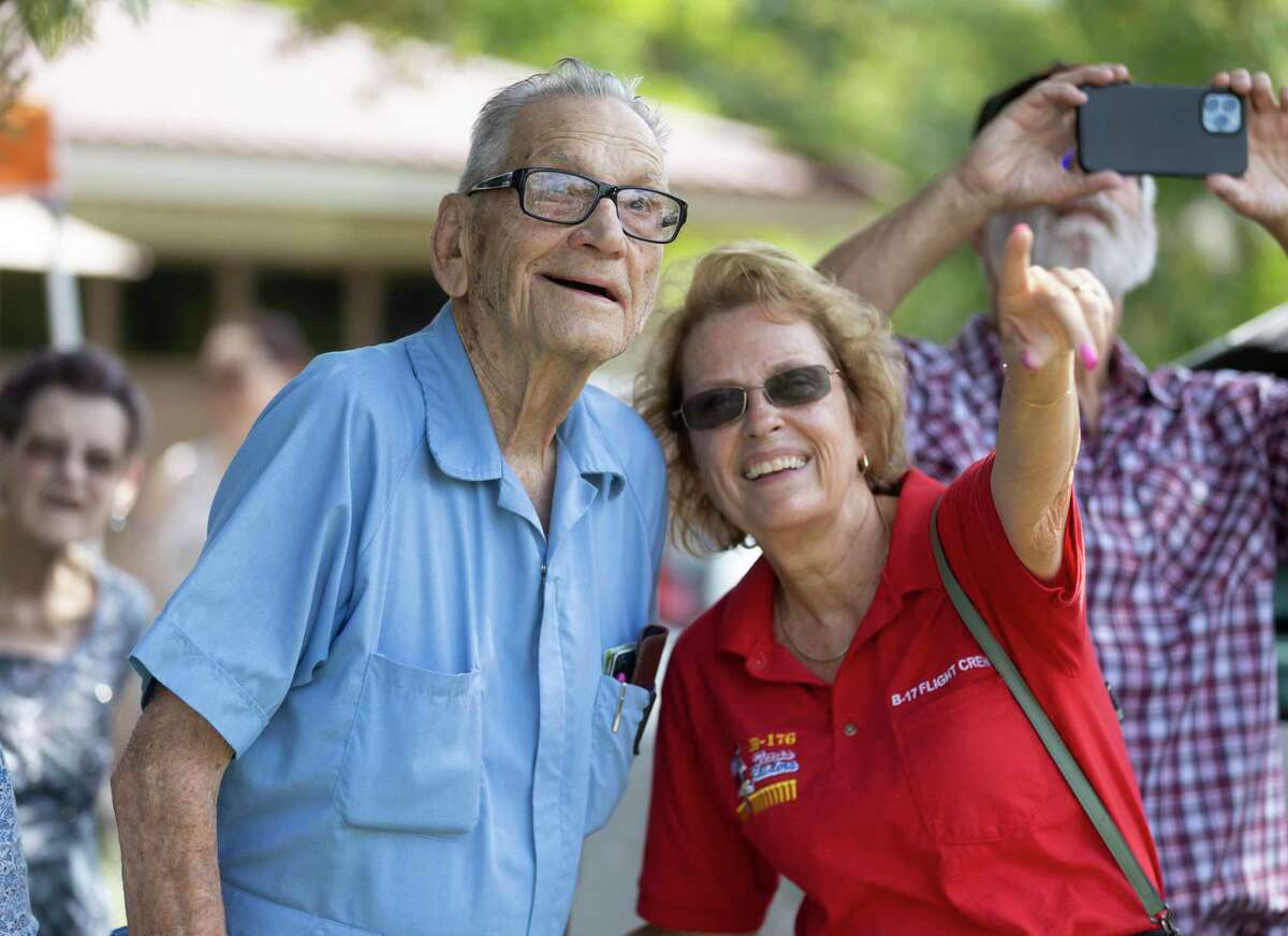 WWII Army Air Corps veteran George Waters, left, and Texas Raiders executive officer Nancy Kwiecien watch as B-17 aircrafts are flown during Waters' 100th birthday celebration June 12 in Conroe. Waters was a B-17 gunner.