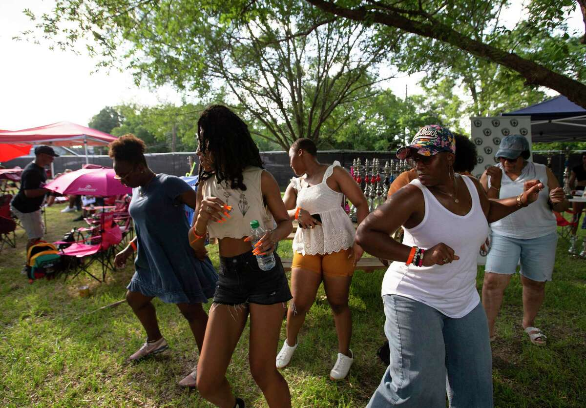 The Smith family enjoys an evening together with live music at the CAMZ Food Truck Park in Acres Homes on Saturday. Also there was a Houston Health Department van and crew available to offer COVID-19 shots.