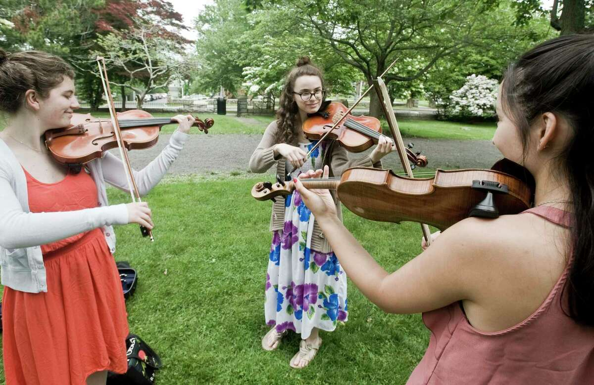 """Former Ridgefield High School students Robin MacDonald, Julia Restivo and Julia Driscoll, provide violin music during the """"Stand Up Against Hate"""" at Ballard Park in Ridgefield on Sunday, June 10, 2018."""