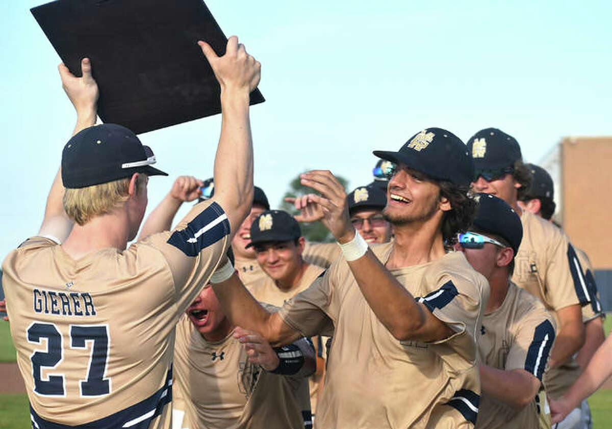 Father McGivney senior Matthew Gierer shows off a plaque to his teammates after Friday's win over Greenfield. The Class 1A sectional championship plaque for baseball will be mailed to the school by the IHSA.