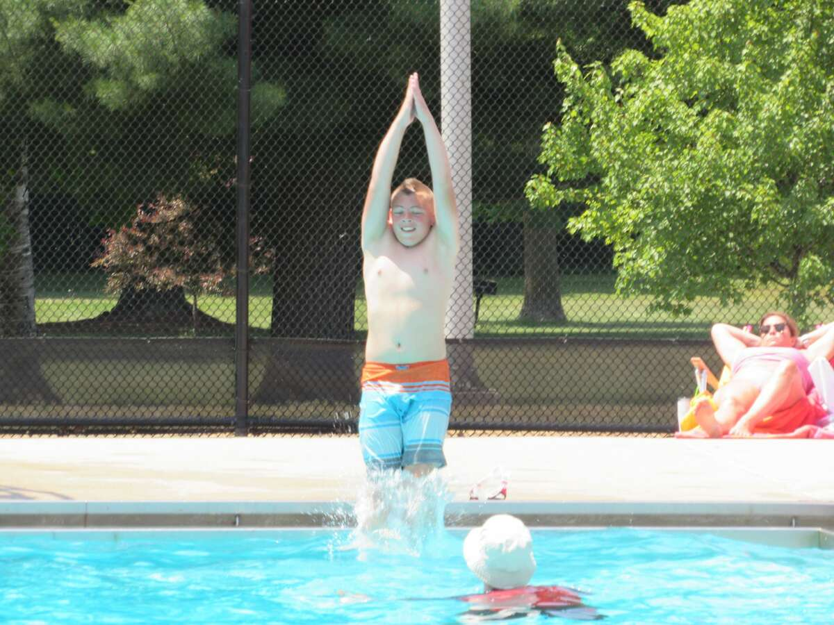Grayson Archangeli, 12, jumps into Plymouth Park Pool on Saturday, June 12.