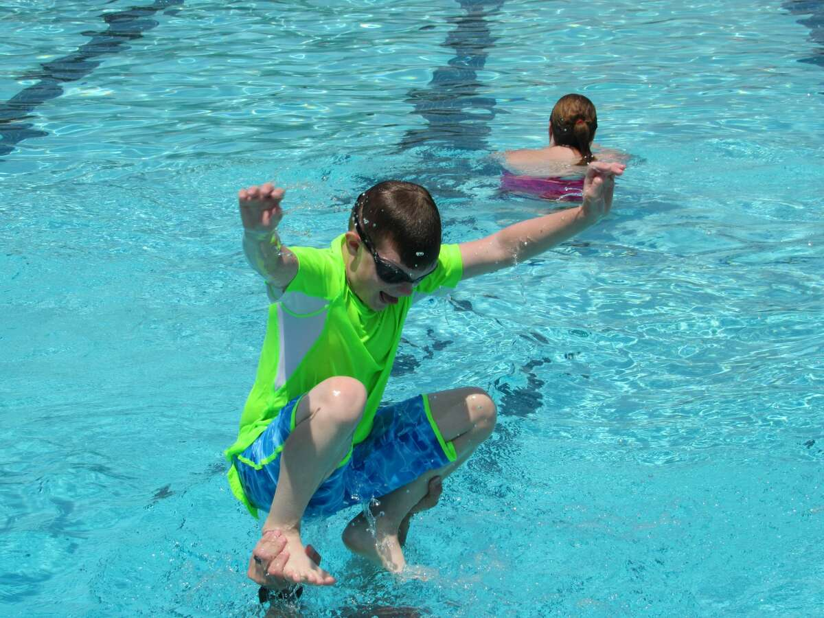 Cal Rishe, 7, balances on his dad's hands, preparing to jump in Plymouth Park Pool on Saturday, June 12.
