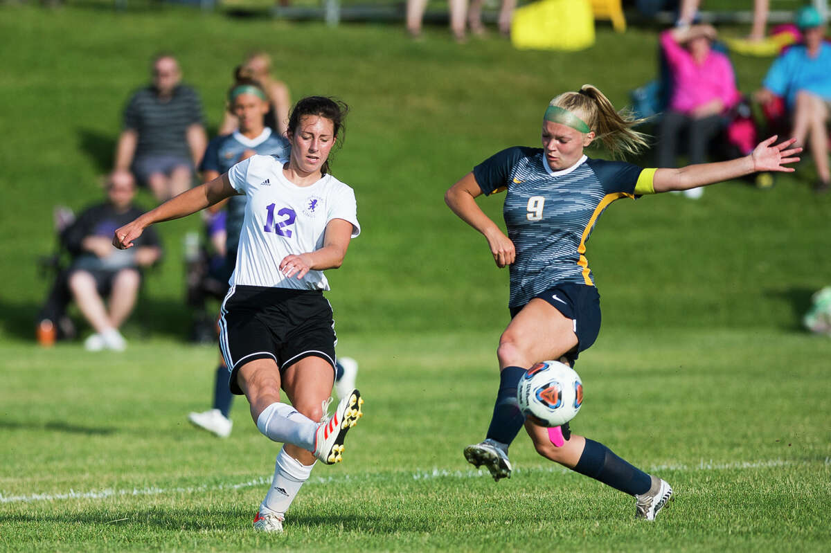 Calvary Baptist's Caroline Holdeman (left) sends the ball downfield during a regional final against North Muskegon on Friday, June 11, 2021.