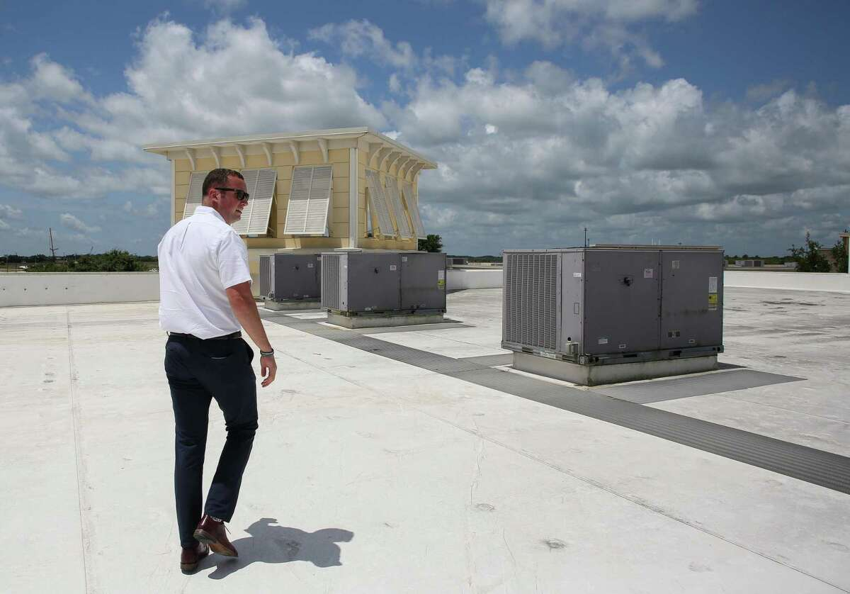 Tanger Outlet Mall marketing manager Oliver Runco walks toward the a section of the mall's roof where they keep honey bees as part of their new urban beekeeping program on Friday, June 11, 2021, in Texas City.