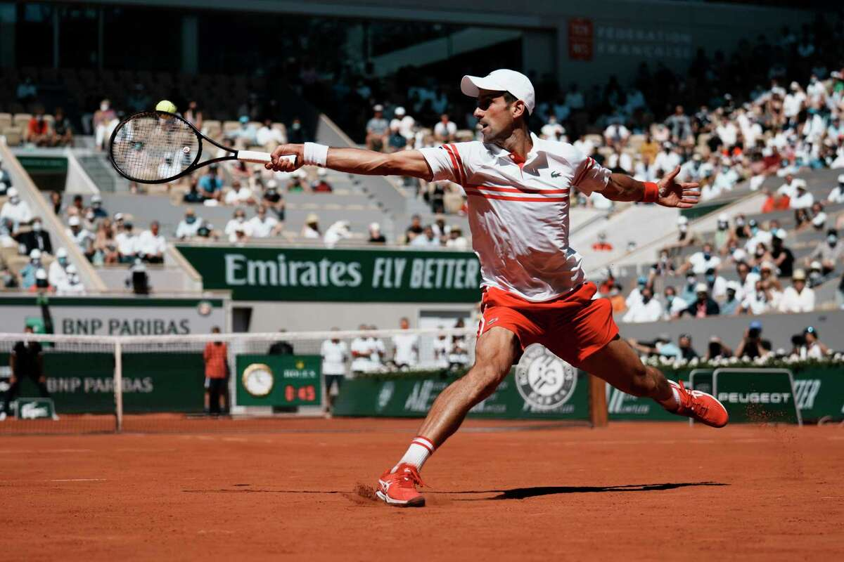 Serbia's Novak Djokovic returns the ball to Stefanos Tsitsipas of Greece during their final match of the French Open tennis tournament at the Roland Garros stadium Sunday, June 13, 2021 in Paris.