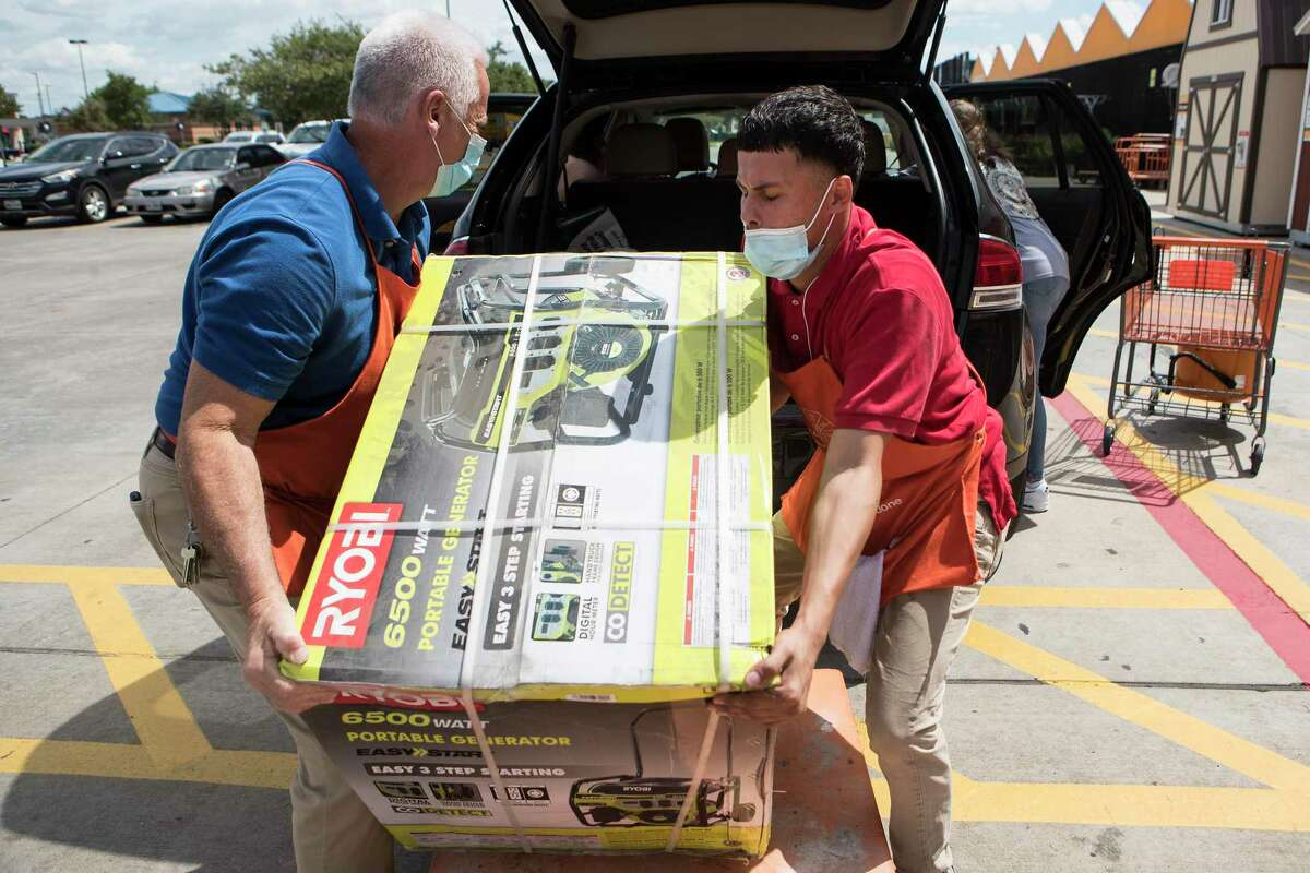 John Prekosovich, left, and Joel Canales loads a portable generator into customer's vehicle at a Home Depot store while preparing for the possible landfall of Hurricane Laura on Tuesday, Aug. 25, 2020 in Houston.