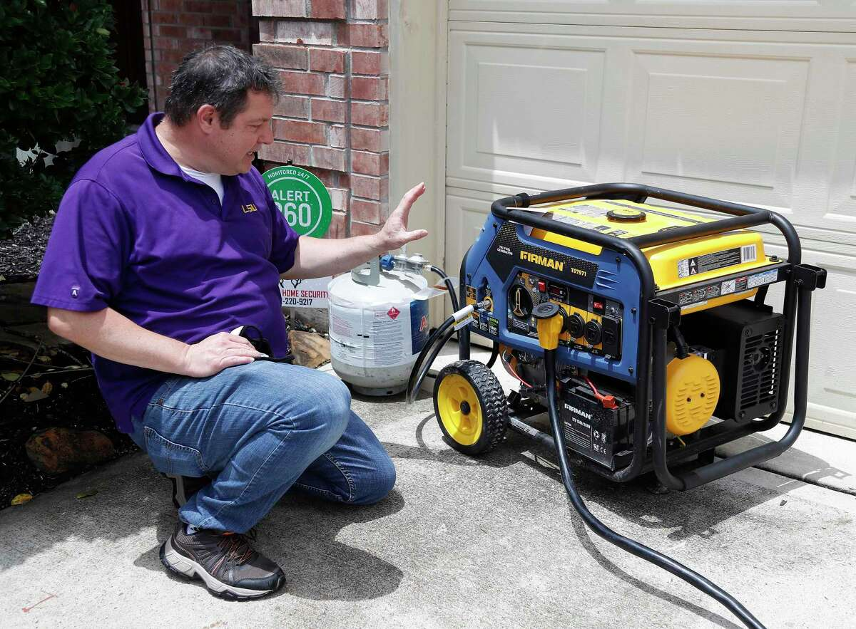 Brian Milan with his portable generator that he has retrofitted to power his home in the event of power outages, Monday, May 24, 2021, in Cypress. Milan, a Cypress resident manages a local Facebook group on retrofitting homes with portable generators.