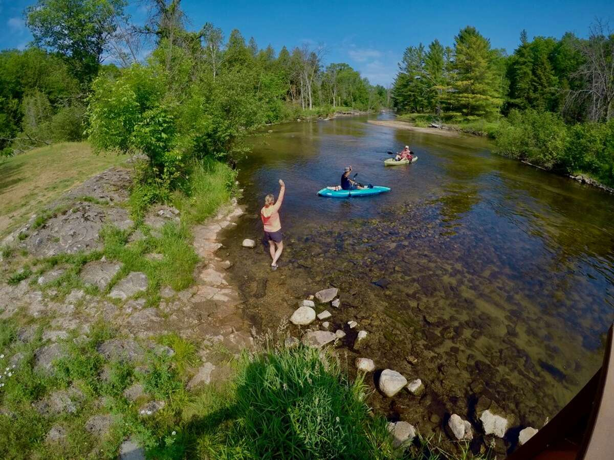 Karin Schwartz, owner of Soggy Dog River Shuttle, waves at patrons as they embark on the Little Manistee River.