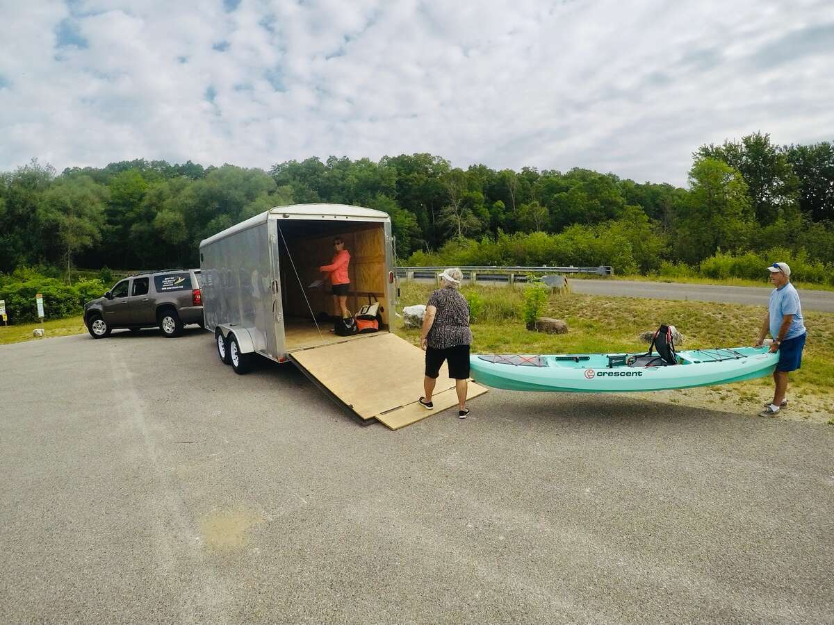 Vacationers unload their kayak after being ferried by Karin Schwartz of Soggy Dog River Shuttle.
