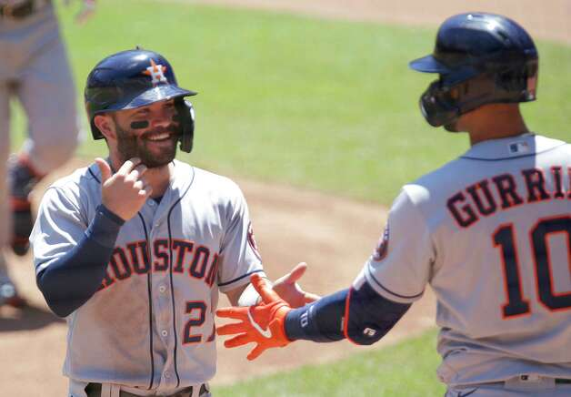 Houston Astros' Jose Altuve (27) is congratulated by teammate Yuli Gurriel (10) after scoring on a sacrifice fly against the Minnesota Twins in the first inning of a baseball game, Sunday, June 13, 2021, in Minneapolis. (AP Photo/Andy Clayton-King) Photo: Andy Clayton-King, Associated Press / Copyright 2021 The Associated Press All Rights Reserved