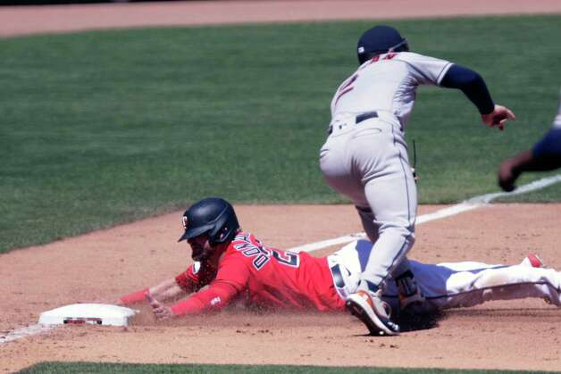 Minnesota Twins third baseman Josh Donaldson (20) slides safely into third base as Houston Astros third baseman Alex Bregman (2) can't make the catch in the sixth inning of a baseball game, Sunday, June 13, 2021, in Minneapolis. The Astros defeated the Twins 14-3. (AP Photo/Andy Clayton-King) Photo: Andy Clayton-King, Associated Press / Copyright 2021 The Associated Press All Rights Reserved