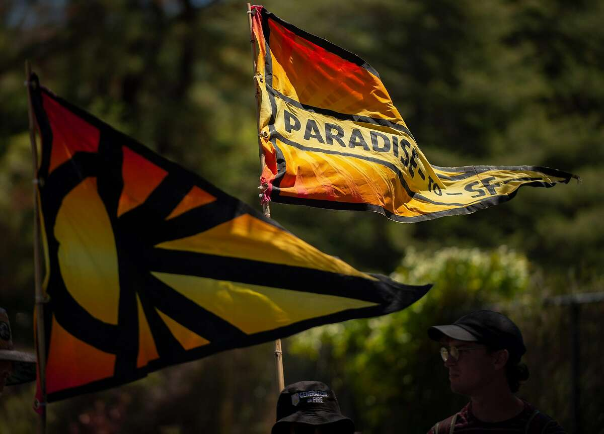 Sunrise Movement climate change flags flutter as the marchers near the Marin Civic Center in San Rafael.
