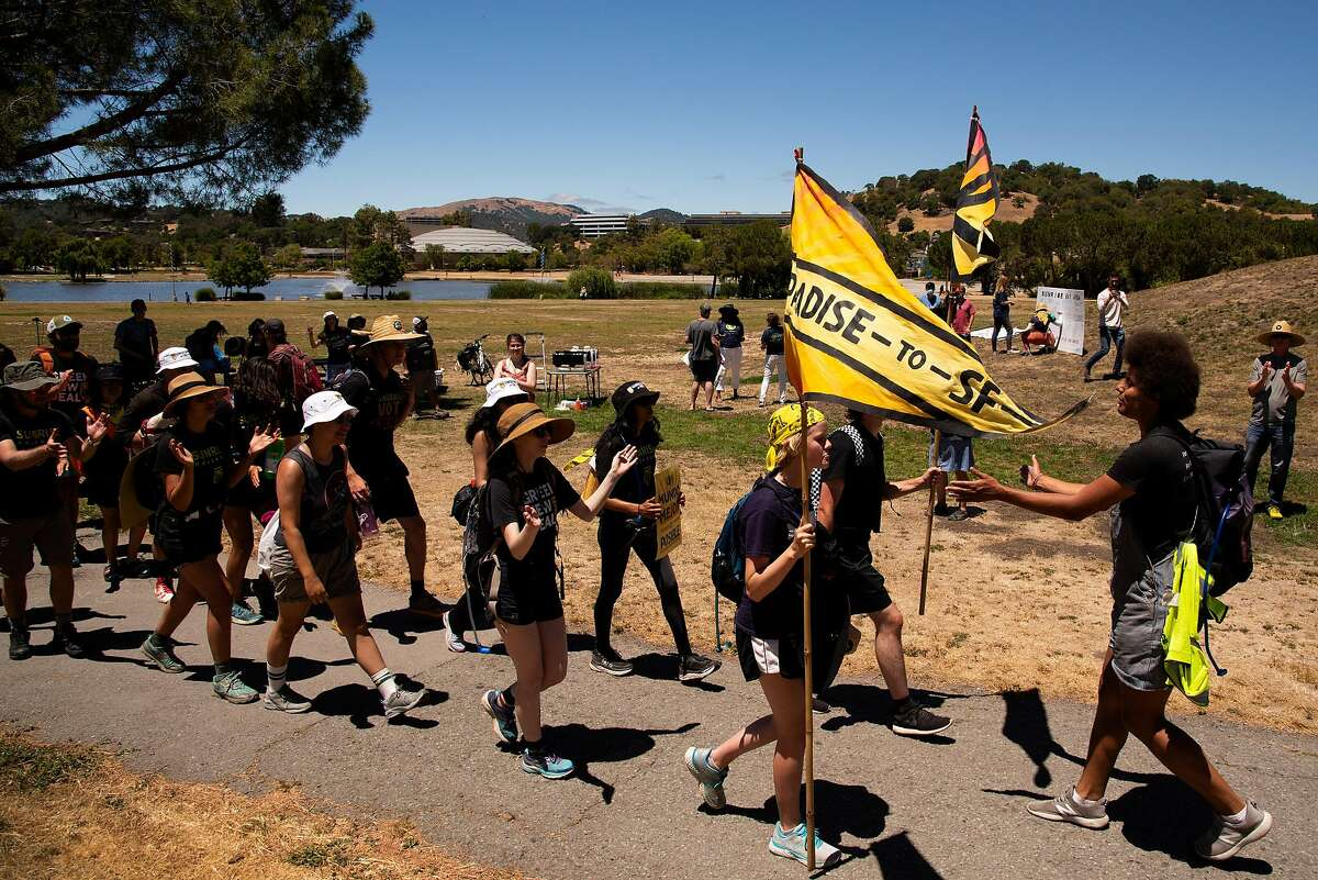 Sunrise Movement activists, pushing for a civilian climate corps, sing on their march from Lagoon Park after meeting with other activists and politicians near the Marin County Civic Center in San Rafael.