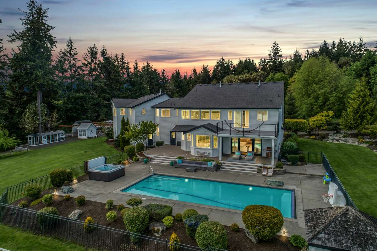 The 5,068-square-foot home opens in the back to a pool, spa, patio and lush landscape beyond.