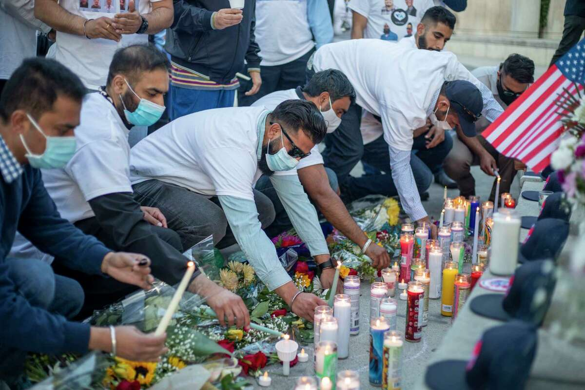 Friends and family of Taptejdeep Singh place candles at a memorial during a vigil in San Jose a day after a mass shooting.