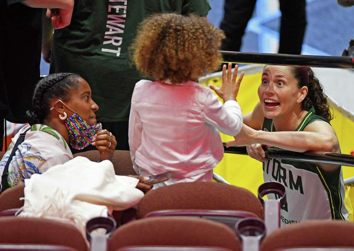 UConn alum and Seattle Storm star Sue Bird, right, talks to Ruby Randle, 5, and her mother Jaime following Sunday's win over the Sun.