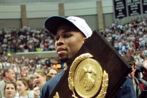 Connecticut basketball team co-captain Ricky Moore carries the winner's trophy during a rally for the team on the UConn campus in Storrs, Conn. Tuesday, March 30, 1999. The UConn men's team defeated Duke 77-74 to win the NCAA Division I men's basketball championship Monday, March 29, 1999. (AP Photo/Carla Cataldi)