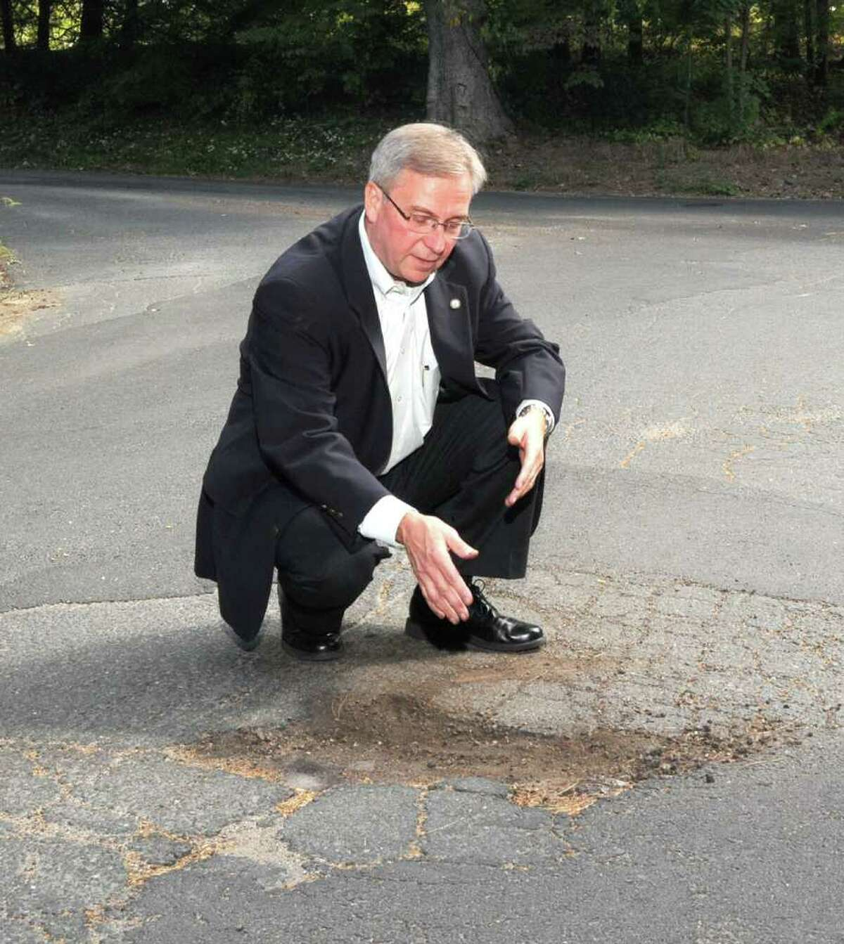 Bethel First Selectman Matt Knickerbocker examines a pothole that exposes three layers of pavement at the intersection of Walnut Hill Road and Weed Road in Bethel on September 13, 2010.