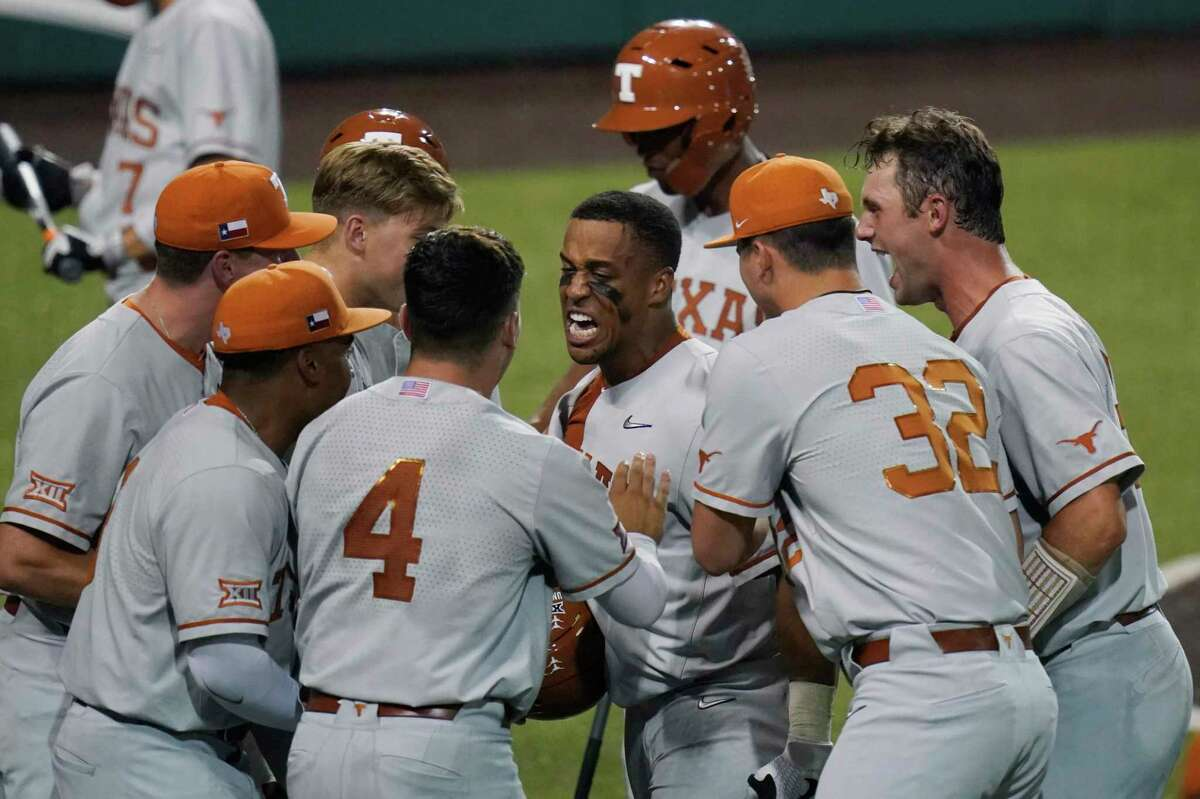 Texas' Cam Williams, center, celebrates a two-run homer against South Florida during the seventh inning of Game 2 of the NCAA Austin Super Regional on Sunday, June 13, 2021.