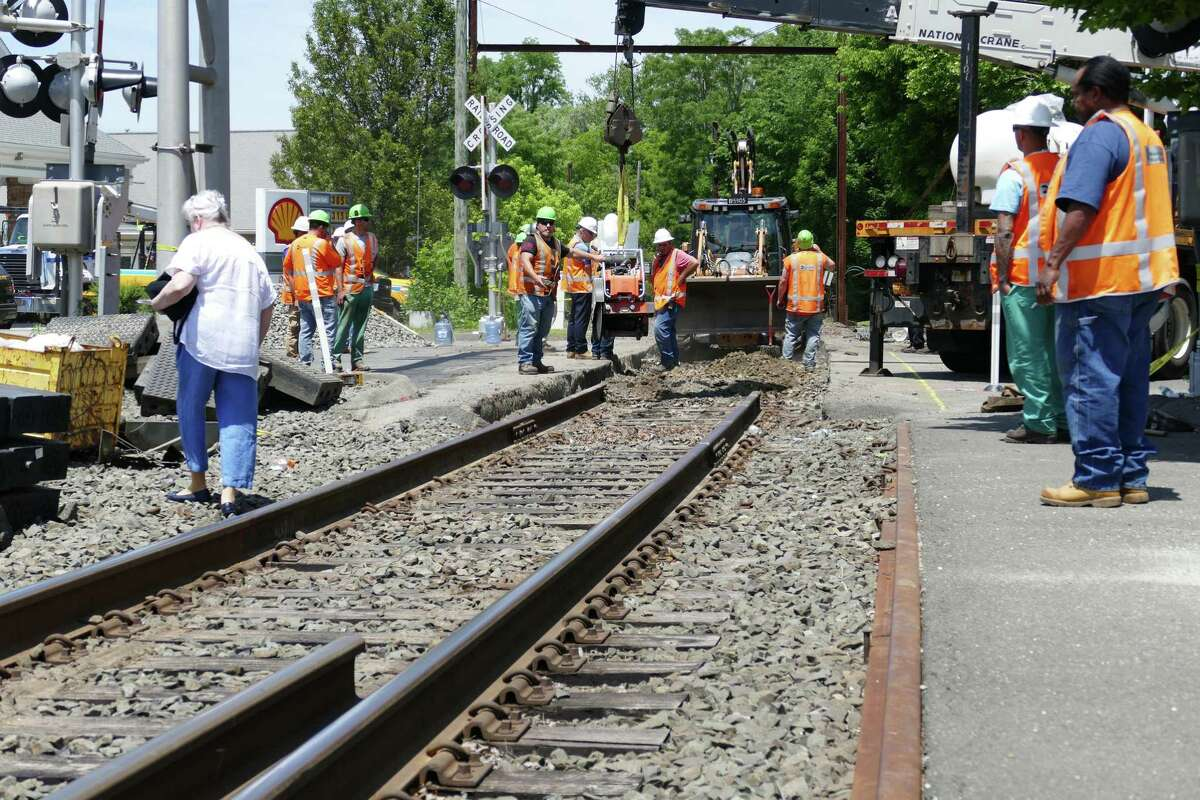 MTA workers repair damage caused by a sinkhole at the Greenwood Avenue rail crossing on Thursday, June 10, 2021.