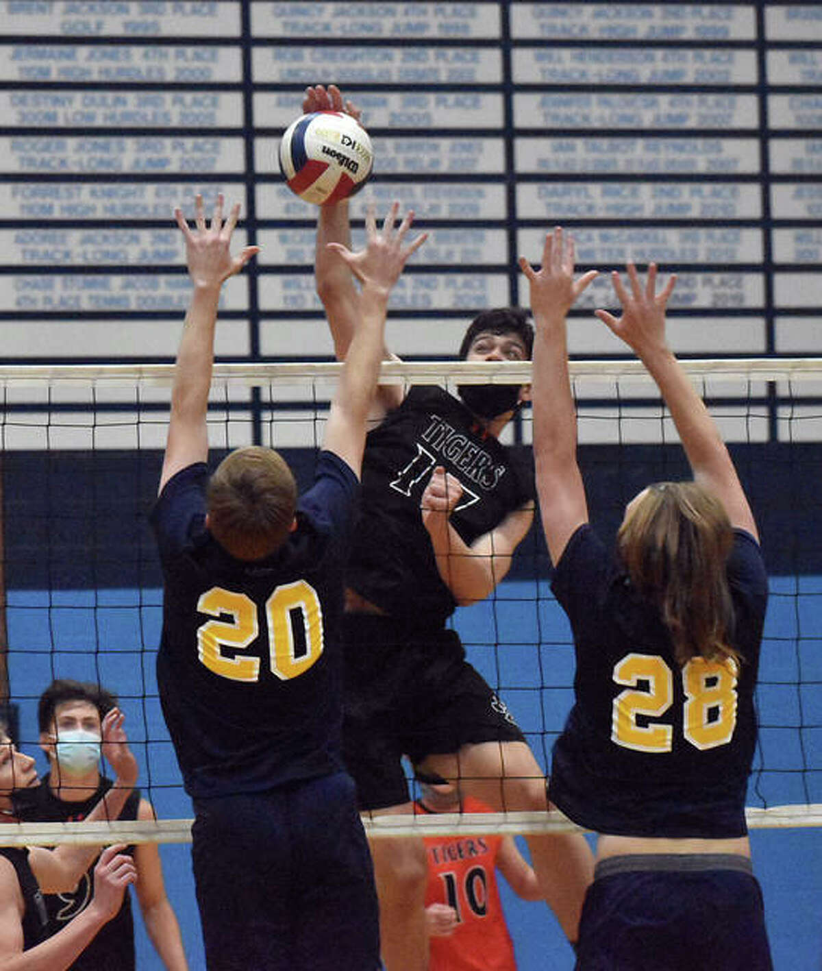 Edwardsville's John Kreke goes up for a kill attempt between two O'Fallon defenders on Saturday in a sectional semifinal at Belleville East in Belleville.