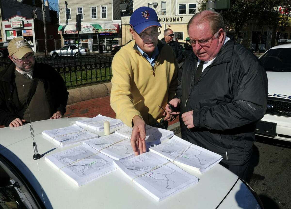 In this 2012 photo, at the Kimberly Triangle: then New Haven Mayor John DeStefano Jr., center, looks over maps of homes in the Hill that were without power, with Fire Chief Michael Grant right and then DeStefano legislative aide Matt Smith left. DeStefano was to visit some of the homes. Grant died in June 2021.