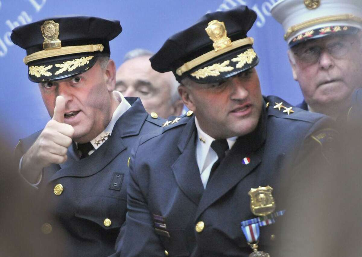 Then Police Chiwf Dean M. Esserman, left, gives a thumbs up to a member of the audience before his swearing in ceremony at New Haven City Hall Friday in Nov. 2011 as the New Haven Police Chief. Sitting with Esserman is Assistant Police Chief John Velleca, center, and New Haven Fire Chief Michael Grant, right.