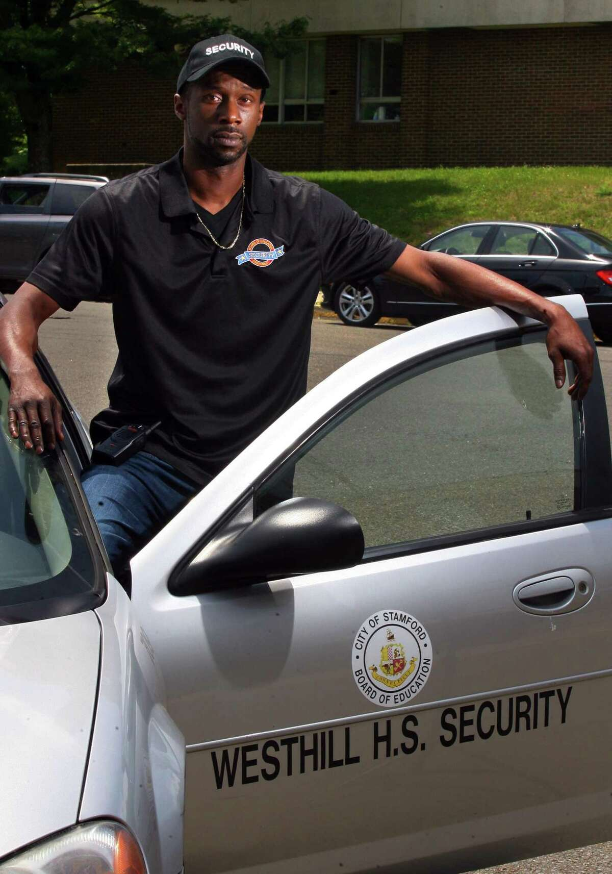 Westhill High School security guard Keith Rosedom, who recently stopped a car from rolling over a visitor, poses at the school in Stamford, Conn., on Friday June 11, 2021.