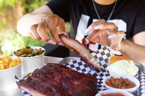 KC's BBQ owner Kristen Davis poses with some of her restaurant's pork ribs with sides in Berkeley, Calif. on June 14, 2021.
