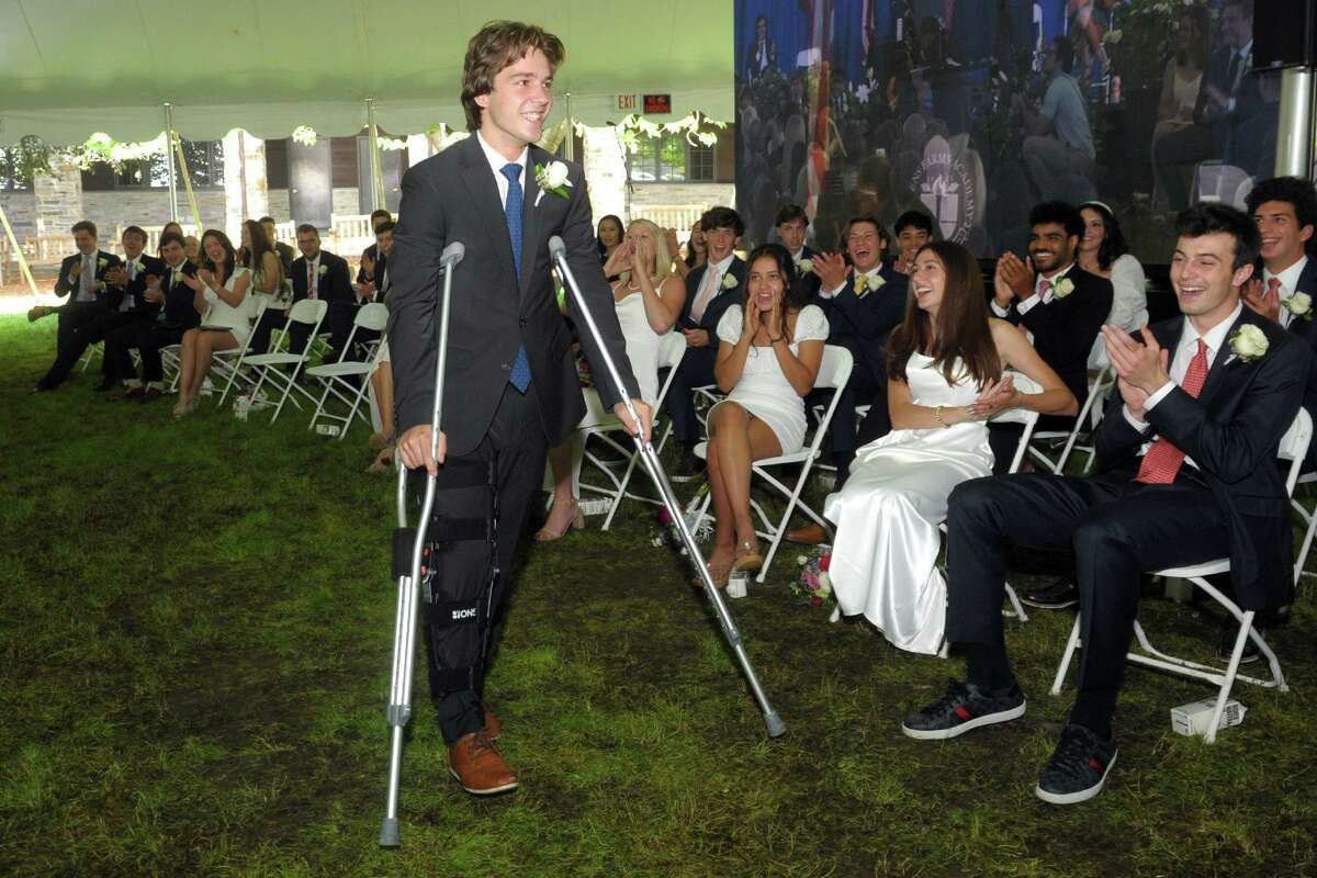 Elek Krizsa steps forward to receive his diploma during commencement for Greens Farms Academy's class of 2021, in Westport, Conn. June 10, 2021.