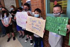 From left, Christina Lorenti listens to speakers as her fourth-grade students Christopher Schlauder, Nathan Silvia, Jose Rangel and Jayce Peluso hold signs of appreciation during a press conference announcing $24 million in funding toward the cost of a new Washington Elementary School in West Haven on June 14, 2021.