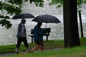 A couple people are seen walking around Iroquois Lake during a rain storm on Monday, June 14, 2021 in Schenectady, N.Y. (Lori Van Buren/Times Union)