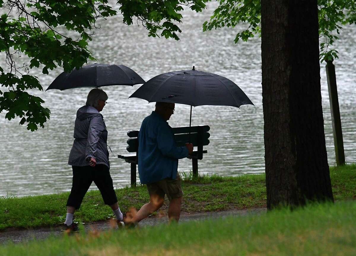 A couple people are seen walking around Iroquois Lake during a rain storm on Monday, June 14, 2021 in Schenectady, N.Y. A flash flood watch has been issued for July 11 to July 12, 2021 that impacts Saratoga and Schenectady counties. (Lori Van Buren/Times Union)