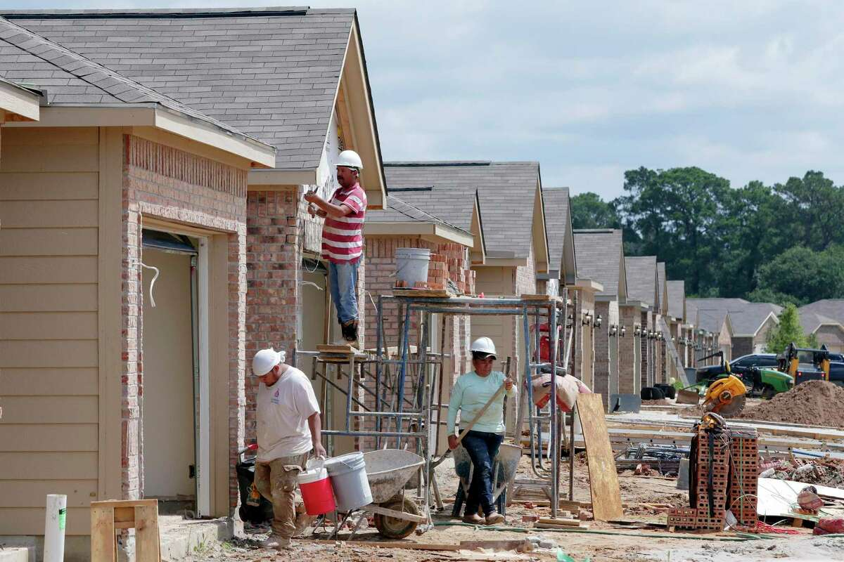 Construction workers lay bricks on the exteriors of new houses by LGI Homes along Lost Lantern Drive in a new section of the Bauer Landing sub-division Thursday, June 3, 2021 in Hockley, TX.