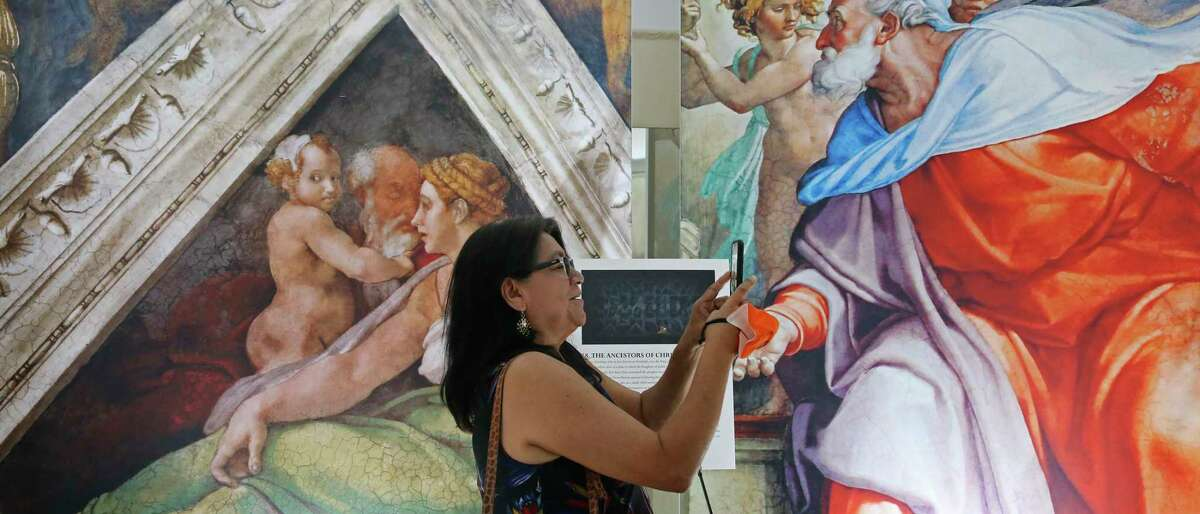 """Maricela Espinoza-Garcia documents the artwork during a preview for """"Michelangelo's Sistine Chapel"""" at Lambermont Events."""