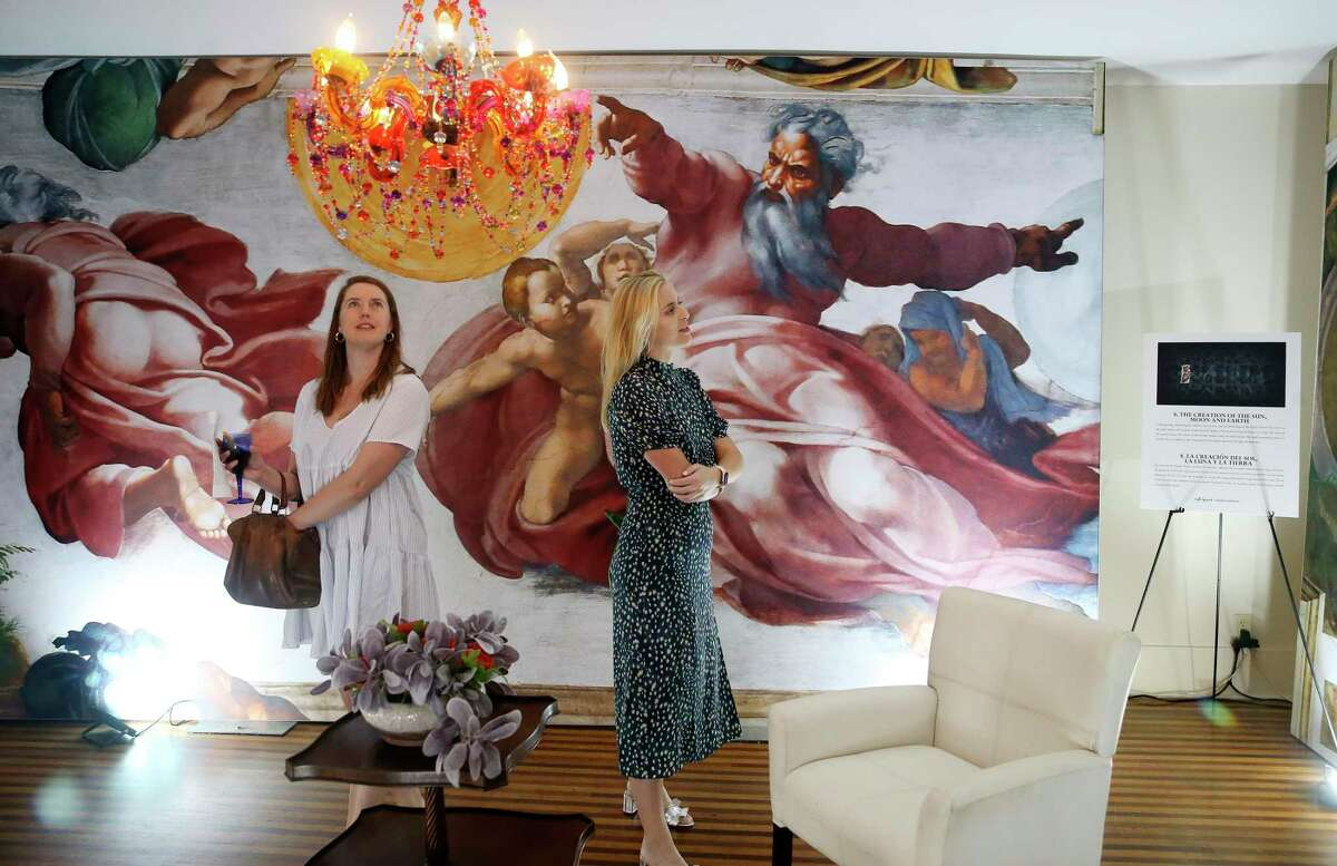 """Isabel Howard, left, and Cody Shown take in the art during a preview for """"Michelangelo's Sistine Chapel"""" at Lambermont Events on East Grayson Street."""