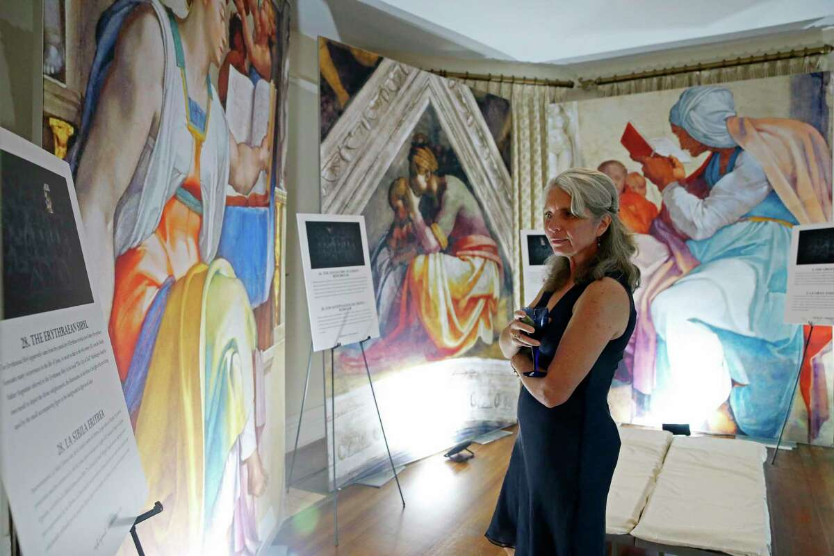 """Annette Paulin attends a preview for """"Michelangelo's Sistine Chapel,"""" which is on display at Lambermont Events. The exhibit consists of 34 high-resolution images of the frescoes that the artist painted in the chapel."""